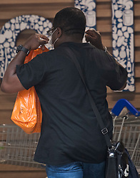 © Licensed to London News Pictures. 24/07/2020. London, UK. A shopper puts on his face mask as he enters Tesco on Goodge Street in central London, on the day that the wearing of mask in shops becomes compulsory. The UK Government has published formal guidance on spaces where the wearing of masks will now be mandatory, including in shops, supermarkets and shopping centres. Photo credit: Ben Cawthra/LNP