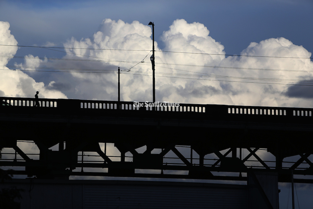 A lone pedestrian crosses the University Bridge over Portage Bay. The heavily used drawbridge connecting the Eastlake neighborhood and University District, which opened in 1919, has endured earthquakes, a 2007 sinkhole on the south side and a rush-hour shutdown by demonstrators in 2011. (Ken Lambert/The Seattle Times)