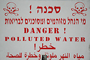 Israel, Bay of Haifa, Kishon River, A sign warning about the polluted water in the river. This river is considered the most polluted river in Israel, it has been the subject of controversy regarding the struggle to improve the water quality. The pollution stems in part from daily contamination for over 40 years with mercury, chemicals, heavy metals by nearby chemical plants.