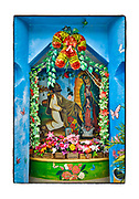 SHOT 2/17/19 11:31:17 AM - A brightly colored roadside capilla outside a home along Highway 307 in Chunyaxche, Quintana Roo, Mexico. The capilla featured a Nuestra Senora de Guadalupe statue and painting as well as multiple flowers on display. The capillas are often dedicated to certain patron saints, such as Nuestra Se√±ora de Guadalupe. Often times they contain prayer candles, pictures, personal artifacts or notes. Muyil (also known as Chunyaxche) was one of the earliest and longest inhabited ancient Maya sites on the eastern coast of the Yucatan Peninsula. It is located approximately 15 kilometres (9.3 mi) south of the coastal site of Tulum, in the Municipality of Felipe Carrillo Puerto in the state of Quintana Roo, Mexico. (Photo by Marc Piscotty / © 2019)