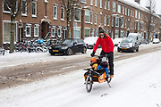 Een man fietst met zijn kinderen in een bakfiets door de sneeuw in Utrecht.<br /> <br /> In Utrecht a man cycles with his children in the cargo bike in the snow.