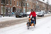 Een man fietst met zijn kinderen in een bakfiets door de sneeuw in Utrecht.<br /> <br /> In Utrecht a man cycles with his children in the cargo bike in the snow.
