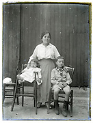 mother posing with children glass plate 1900s