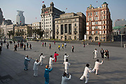 The BundMorning exercisers practices Taichi in a square on the bund, with the colonial-era bank and hotel buildings as the backdrop in Shanghai, China on 13 October 2013. The Bund, along with the contrast of the modern skyline across the Huangpu River in Pudong's Lujiazui Financial District, is one of the most iconic tourist destination in China and possibly the world.