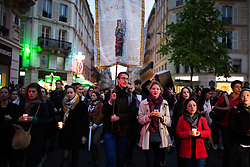 """People praying with candles and holding a saints Clotilde sign during an evening of prayer and songs organized by Catholics community the day after Notre Dame Cathedral blaze with a march organized from Saint-Sulpice church to Saint Michel and finally next to Notre Dame Cathedral in Paris early on April 16 the day after the beginning of the fire , 2019. A huge fire that devastated Notre-Dame Cathedral is """"under control"""", the Paris fire brigade said early on April 16 after firefighters spent hours battling the flames. Photo by Raphael Lafargue/ABACAPRESS.COM"""