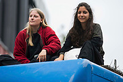 Environmental activists from Extinction Rebellion sit on top of a blue van used to block Mansell Street to the north of Tower Bridge during an Impossible Tea Party event on 30th August 2021 in London, United Kingdom. Extinction Rebellion were drawing attention to financial institutions funding fossil fuel projects whilst calling on the UK government to cease all new fossil fuel investment with immediate effect on the eighth day of their Impossible Rebellion protests in London.