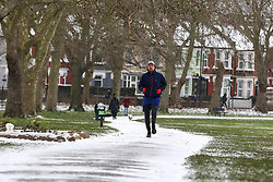 © Licensed to London News Pictures. 08/02/2021. London, UK. A jogger braves the snow, freezings temperatures and strong winds in north London. The Met Office has issued yellow warnings for snow as cold air from Russia and Eastern Europe continues across the UK. Photo credit: Dinendra Haria/LNP