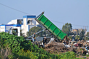 Illegal Littering - a truck dumps trash in a vacant field