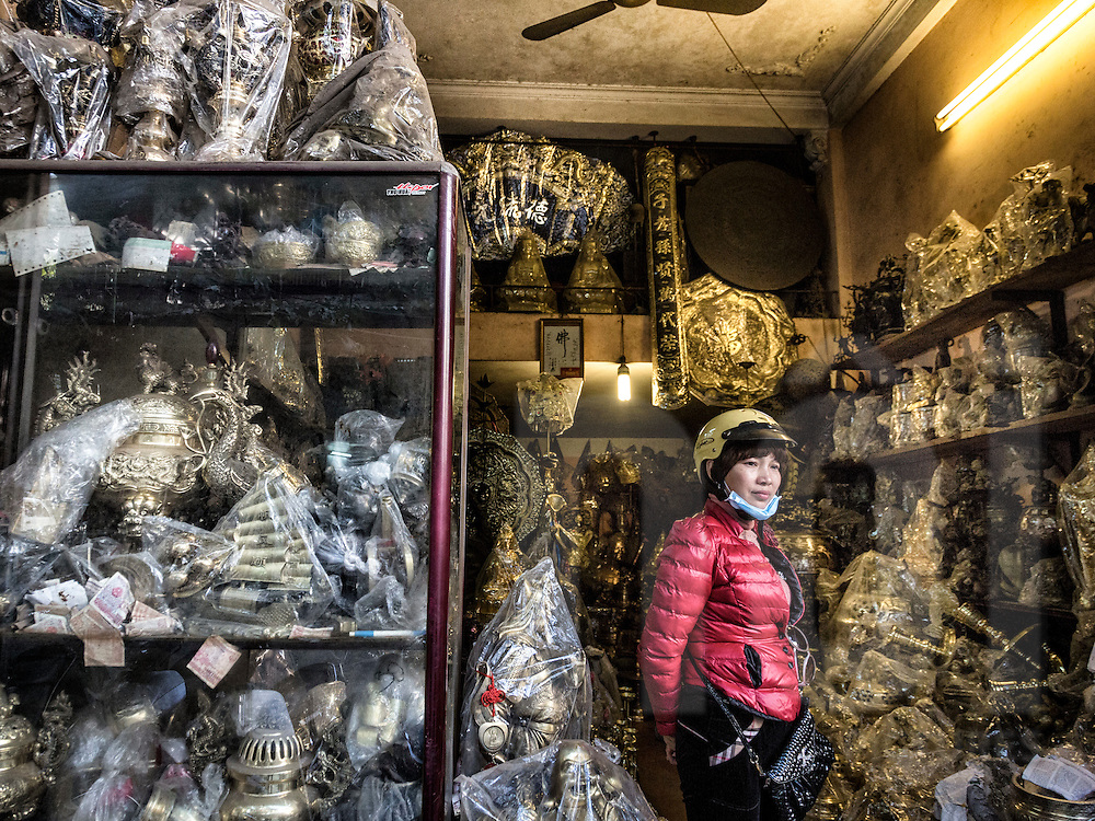 A Vietnamese woman wearing a helmet stands amidst an abundance of copper goods in a shop along Hang Dong street known for copper products in Hanoi's Old Quarter, Vietnam, Southeast Asia