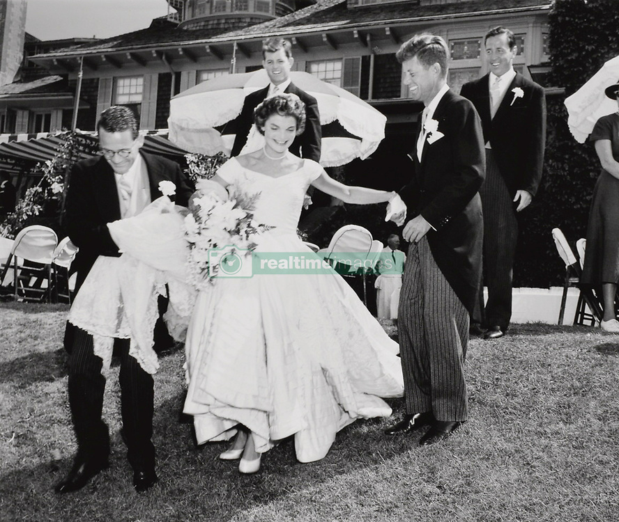 May 16, 2017 - U.S. - File Photo - Newlyweds John and Jacqueline Kennedy with Jackie playfully descending a small hill at Hammersmith Farm after taking wedding party photos, with a young Ted Kennedy looking on in the background. In very fine museum-quality condition. John and Jacqueline married at historic St. Mary's Church in Newport, Rhode Island, on September 12, 1953. An iconic image of the future first lady and arguably the most publicized photograph from their wedding.. In commemoration of JFK's 100th birthday on May 29, 2017, RR Auction has curated an once-in-a-lifetime assortment of Kennedy artifacts, signed material, and photographs to celebrate the life of America's beloved 35th president. The more than 175 lots cover; JFK's early years, the transition to his congressional and senatorial careers, and 'The 1,000 Days of Camelot,' Kennedy's storied tenure as president. The special online offering is scheduled to begin on May 11 and will conclude on May 18, 2017. The R. Paloger photographs depict a fascinating and crucial period in JFK's life from 1946