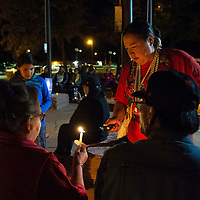 Navajo Nation Council Delegate Amber Kanazbah Crotty lights a candle for community members in attendance at a candlelight vigil in recognition of the National Day of Remembrance for Murder Victims Wednesday, September 25, in Window Rock at the Navajo Nation Council Chamber.