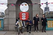 A quartet of two singers and two musicians perform on Southwark Bridge during Thames Festival. A man playing an accordion and a guitarist accompany the two young ladies whose song is being performed in the middle of this city bridge that has been closed to traffic to host part of the annual celebration of London life and nautical culture. A life ring cover is located behind them because many attempt to take their lives in the Thames every year and in the background is the capital's newest addition to its cityscape: The Shard at London Bridge. Coloured bunting hangs from lamp posts above their heads.