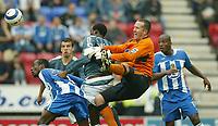 Photo: Aidan Ellis.<br /> Wigan Athletic v Newcastle United. The Barclays Premiership. 15/10/2005.<br /> Wigan keeper john Filan is fouled by Newcastle's Shola Ameobi