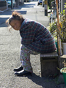 elderly lady sitting outside warming herself in the morning sun