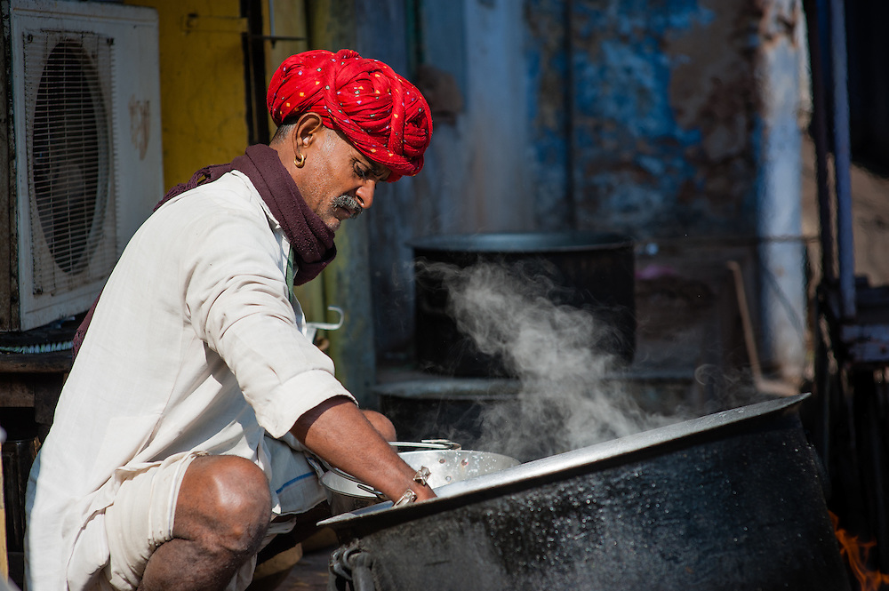 Rajasthani man with red turban cooking in big pot (India)