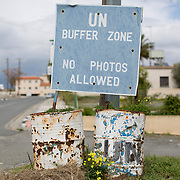 A sign marking the United Nations buffer zone is seen in the village of Pyla in the Larnaca District of Cyprus March 11, 2014.  It is one of only four villages located within the United Nations Buffer Zone and is a mixed community with both Greek and Turkish Cypriots living side by side. This year marks 40 years since the Cyprus National Guard staged a coup in Cyprus and the subsequent Turkish military intervention, which escalated a civil war between the Greek and Turkish Cypriot communities on the island. After the ceasefire a heavily restricted UN controlled Buffer Zone between the north and south of the island was put into operation. It stretches 180 Km across the whole island measuring 7.4 km at its widest and 3.3 meters at its narrowest point. It is restricted to the general public and no Greek or Turkish Cypriots are allowed inside. REUTERS/Neil Hall (BRITAIN)
