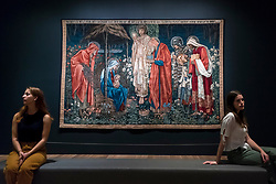 """© Licensed to London News Pictures. 22/10/2018. LONDON, UK. Staff members sit next to """"The Adoration of the Magi"""", 1894, by Edward Burne-Jones.  Preview of the largest Edward Burne-Jones retrospective to be held in a generation at Tate Britain.  Burne-Jones was a pioneer of the symbolist movement and the only Pre-Raphaelite to achieve world-wide recognition in his lifetime.  The exhibition runs 24 October to 24 February 2019.  Photo credit: Stephen Chung/LNP"""