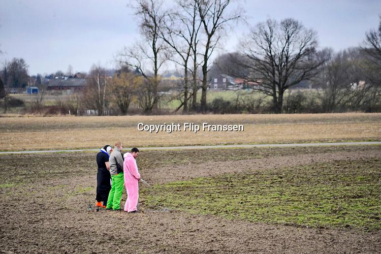 Nederland, Groesbeek, 3-3-2019Jonge mannen staan met carnaval te plassen aan de rand van het dorp in een akker . Foto: Flip Franssen