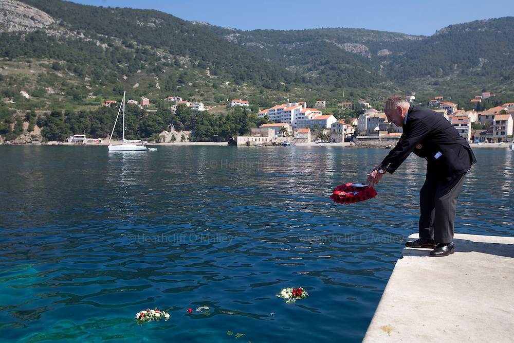 Mcc0031516 . Daily Telegraph..A commemorative wreath is thrown into the Adriatic sea by John Rivett Coastal Forces off the jetty in the fishing town of Komiza on the island of Vis where British forces were based during WWII .. A reunion of British WW2 Veterans, probably for the last time. They are some of the last survivors of an Allied combined garrison of Royal Navy, Royal Marine Commandos, Army and Royal Air Force personnel who took over the Island of Vis in 1943 and held it until the end of the War. From here they harried Axis Forces in what was Yugoslavia, providing supply drops to the Partisans and, at one point, refuge for Marshall Tito when he was nearly captured by German Forces ...19 May 2011 Vis, Croatia