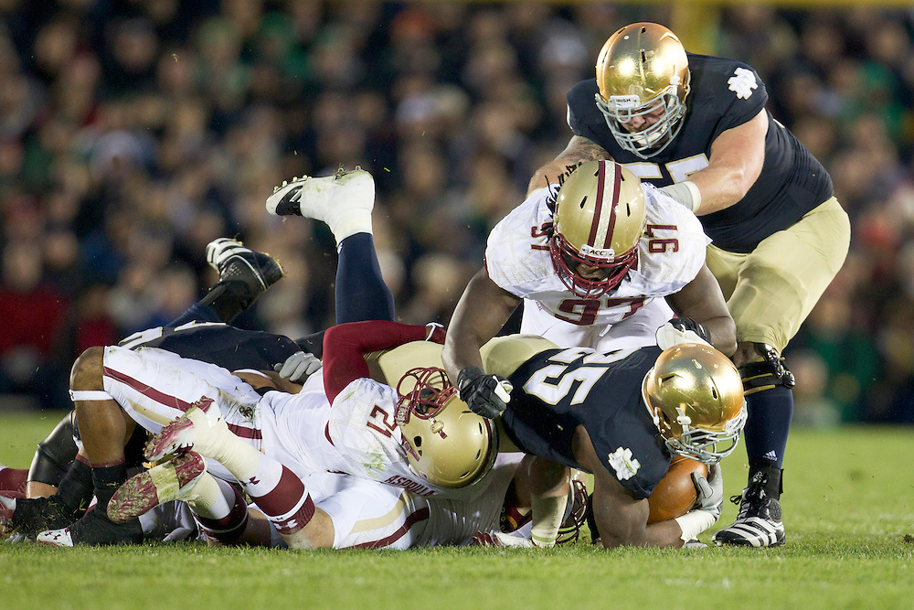 Notre Dame tailback Jonas Gray (#25) is tackled by a host of Boston College defenders during second quarter of NCAA football game between Notre Dame and Boston College.  The Notre Dame Fighting Irish defeated the Boston College Eagles 16-14 in game at Notre Dame Stadium in South Bend, Indiana.