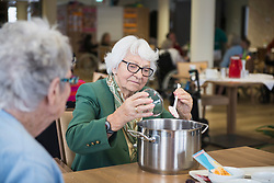 Senior woman preparing marmalade in rest home