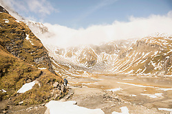 Two hikers walking at riverside, Grossglockner mountain with Glacier Pasterze, Hohe Tauern National Park, Carinthia, Austria