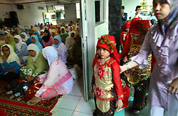 Young female performers dressed in traditional costume prepare to dance at the mass circumcision timed to honor the Prophet Mohammed's birthday in Bandung, Indonesia on April 23, 2006. All the girls were circumcised in years prior. The families of 248 girls were given money to have their children circumcised at this event.  While religion was the main reason for circumcisions, it is believed by some locals that a girl who is not circumcised would have unclean genitals after she urinates which could lead to cervical cancer. It is also believed if one prays with unclean genitals their prayer won't be heard. The practitioners used scissors to cut the hood and tip of the clitoris. The World Health Organization has deemed the ritual unnecessary and condemns such practices.