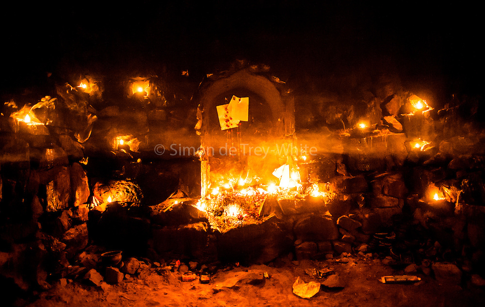 "11th December 2014, New Delhi, India. Layers of smoke hang in the air in a chamber where believers pray, make offerings and ask for wishes to be granted by Djinns in the ruins of Feroz Shah Kotla in New Delhi, India on the 11th December 2014<br /> <br /> PHOTOGRAPH BY AND COPYRIGHT OF SIMON DE TREY-WHITE a photographer in delhi<br /> + 91 98103 99809. Email: simon@simondetreywhite.com<br /> <br /> People have been coming to Firoz Shah Kotla to leave written notes and offerings for Djinns in the hopes of getting wishes granted since the late 1970's. Jinn, jann or djinn are supernatural creatures in Islamic mythology as well as pre-Islamic Arabian mythology. They are mentioned frequently in the Quran  and other Islamic texts and inhabit an unseen world called Djinnestan. In Islamic theology jinn are said to be creatures with free will, made from smokeless fire by Allah as humans were made of clay, among other things. According to the Quran, jinn have free will, and Iblis abused this freedom in front of Allah by refusing to bow to Adam when Allah ordered angels and jinn to do so. For disobeying Allah, Iblis was expelled from Paradise and called ""Shaytan"" (Satan).They are usually invisible to humans, but humans do appear clearly to jinn, as they can possess them. Like humans, jinn will also be judged on the Day of Judgment and will be sent to Paradise or Hell according to their deeds. Feroz Shah Tughlaq (r. 1351–88), the Sultan of Delhi, established the fortified city of Ferozabad in 1354, as the new capital of the Delhi Sultanate, and included in it the site of the present Feroz Shah Kotla. Kotla literally means fortress or citadel."