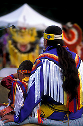 Back of American Indian Father and Son Sit Together in Costume