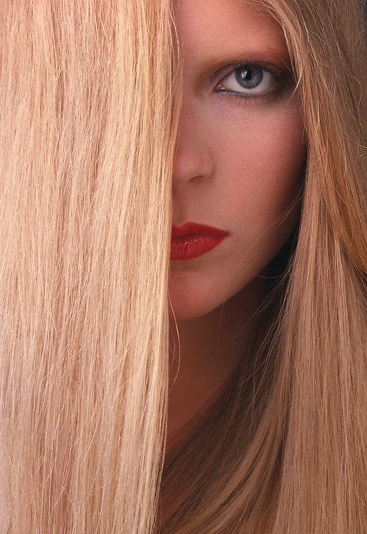 Blond haired woman's face with hair covering half of her face. Woman with red lips.