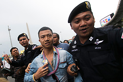 © Licensed to London News Pictures. 27/05/2014. A PDRC supporter is taken away by police for his own safety after taunting anti-coup protestors during a Anti-Coup protest in Bangkok Thailand. yesterday Thailand's King formally approved Thai army chief General Prayut Chan-O-Cha as head of the nation's new military junta.  Photo credit : Asanka Brendon Ratnayake/LNP