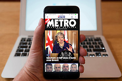 Using iPhone smartphone to display headlines from Metro newspaper in London