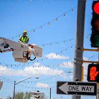 042915       Cable Hoover<br /> <br /> City of Gallup Electric employee Ryan Smith rides a lift to hang more twinkle lights across Coal Avenue in downtown Gallup Wednesday.