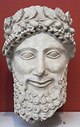 Limestone head of a statue of a bearded worshipper.  Made in Cyprus 475-450 BC.  From the sanctuary of Apollo at Idalion.  He wears a laurel wreath with beads or acorns.  His hair has a fringe of spiral curls and is combed into tresses on the crown which fall down the neck.