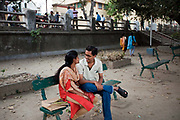 A young couple sit and talk together on the Strand by the Hoogley River, Chandannagar at dusk, India