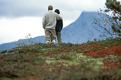 Hiker couple enjoying view from mountaintop.<br /> Beiarn/ Norway.<br /> Released.