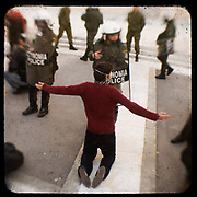 A teenager protesting in front of a riot policeman in Syntagma square. <br /> <br /> Following the murder of a 15 year old boy, Alexandros Grigoropoulos, by a policeman on 6 December 2008 widespread riots, protests and unrest followed lasting for several weeks and spreading beyond the capital and even overseas<br /> <br /> When I walked in the streets of my town the day after the riots I instantly forgot the image I had about Athens, that of a bustling, peaceful, energetic metropolis and in my mind came the old photographs from WWII, the civil war and the students uprising against the dictatorship. <br /> <br /> Thus I decided not to turn my digital camera straight to the destroyed buildings but to photograph through an old camera that worked as a filter, a barrier between me and the city.
