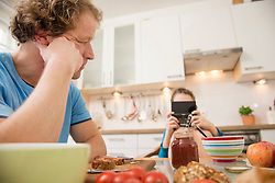 Father looking at son playing video game at breakfast table
