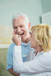 Mature woman feeding food to mature man