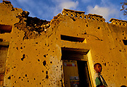 A child outside his house that clearly shows the scars of the battle for Hargeisa, the capital of the Self Declared Independent country of Somaliland.