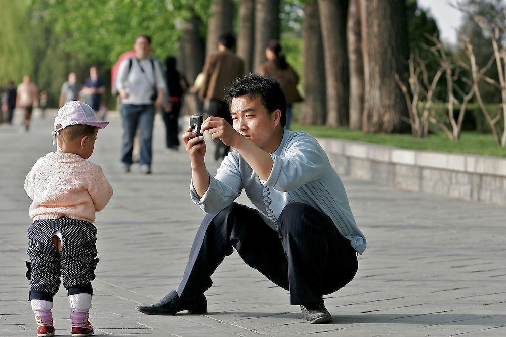 A Visitor and young child at the Summer Palace walk along the Kunming Lake.  The Summer Palace in north west Beijing, China was built in the Jin Dynasty.  The Summer Palace is over 700 acres, 3/4 of which is the Kunming Lake.