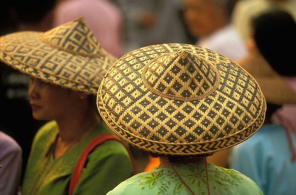 Shan women wears traditional bamboo hats at a procession during Poy Sang Long, the yearly ordination of novice monks, Mae Hong Son, Thailand.