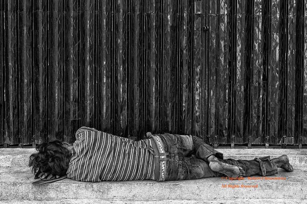 Home Street Home (B&W): A homeless man finds a moment's sleep, using his flip flops as a pillow, on the stairs of a locked doorway, Wat Ounalom, Phnom Penh Cambodia.