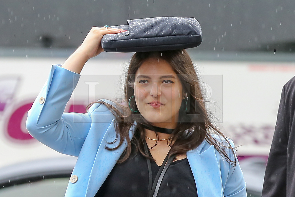 © Licensed to London News Pictures. 18/06/2019. London, UK. A woman shelters from the rain under her purse in Westminster. The Met Office has issued a yellow weather warning for London as torrential rain, hail and lightning is forecasted. Photo credit: Dinendra Haria/LNP