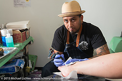 Angel Guarjardo working at Old School Tattoo on Main Street during the 75th Annual Sturgis Black Hills Motorcycle Rally.  SD, USA.  August 1, 2015.  Photography ©2015 Michael Lichter.