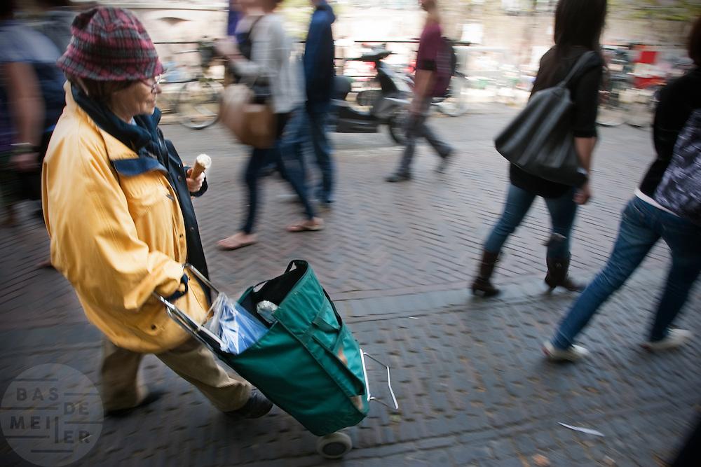 Een oudere vrouw loopt met boodschappenwagen en een ijsje in haar hand door de binnenstad van Utrecht