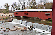 Bridgeton Historic District, Indiana: Bridgeton Covered Bridge (245 feet long) was rebuilt in historically accurate Burr Arch style in 2006 over Big Raccoon Creek (replacing 1868 bridge burnt by arson in 2005) on Bridgeton Road, Parke County, Indiana, USA. Bridgeton Mill was established 1823, rebuilt 1870, and is the oldest continuously operating mill west of the Allegheny Mountains. The mill grinds wheat into flour and corn into meal with 200 year-old French Buhr stones. Red and white painted wood. Dam and spillway.