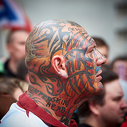 © Licensed to London News Pictures.  20/09/2014. LONDON, UK. A heavily tattooed member of the English Defence League (EDL) listens to a speech opposite Downing Street. The group is attempting to highlight it belief that  Muslim sexual grooming gangs are abusing English girls. Earlier this week a home office official warned of the rise of the far right. Photo credit: Cliff Hide/LNP