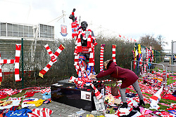 A general view of a fan adding to the memorial surrounding the Gordon Banks statue outside the bet365 Stadium, Stoke.