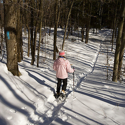 A woman snowsoes on the Cross-Rivendell Trail in West Fairlee, Vermont.  Bald Top Mountain.  Winter.